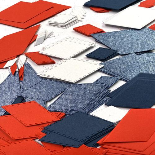 papírové kosočtverce různých velikostí v červené, modré a bílé barvě vyřezané na Big Shotu čablonou CR1449 od Marianne Design
