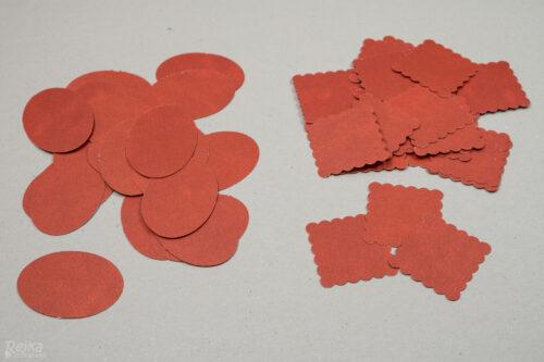 Oválky a vroubkované čtverce vyražené razidlem na papír z červené čtvrtky připravené na adventní kalendáře z balicího papíru.