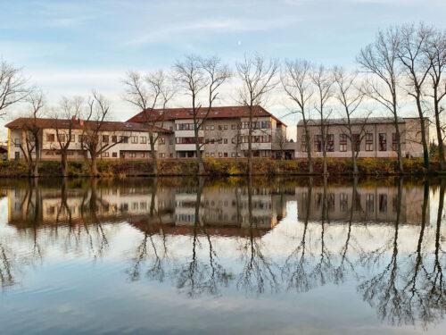 ZŠ, MŠ a ZUŠ Jesenice s odleskem na hladině rybníka Pančák, fotka ze série podzimní fotografie z Jesenice
