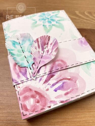 Minialbum zavřené papírovou rozetou s malými papírovými pírky.