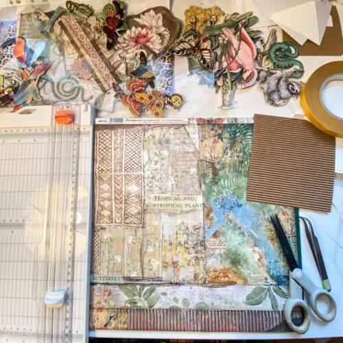 Výstřižky, papíry, nůžky, řezačka, lepicí páska - k výrobě motýlího exploding boxu je vše připraveno.