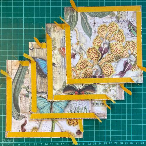 Čtvercové panely ze scrapbookového papíru připravené na nalepení na exploding box.